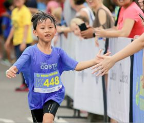 Kid-giving-high-five-to-spectators-while-running
